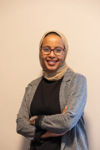 A young woman wearing a hijab and glasses smiles toward the camera; her arms are crossed in front of her.